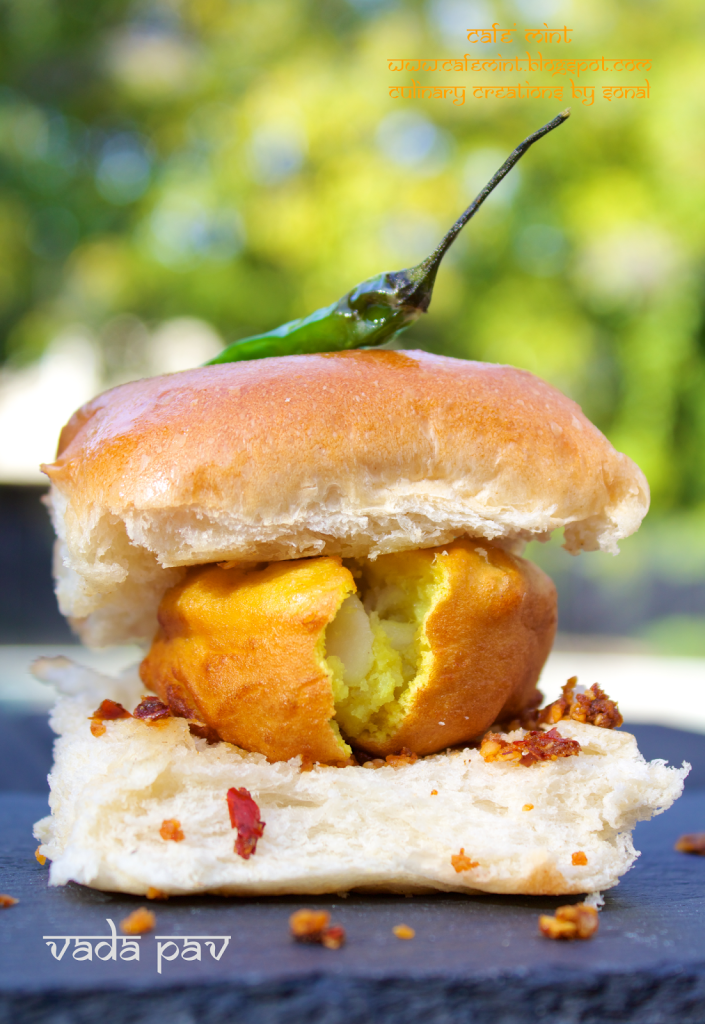 A vada pav with red chutney on a black plate with green chili on top