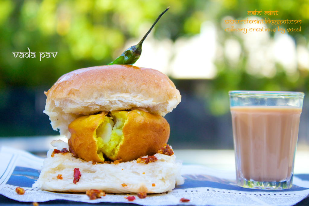 A vada pav with red chutney with green chili on top and a glass of tea on the side served on a newspaper