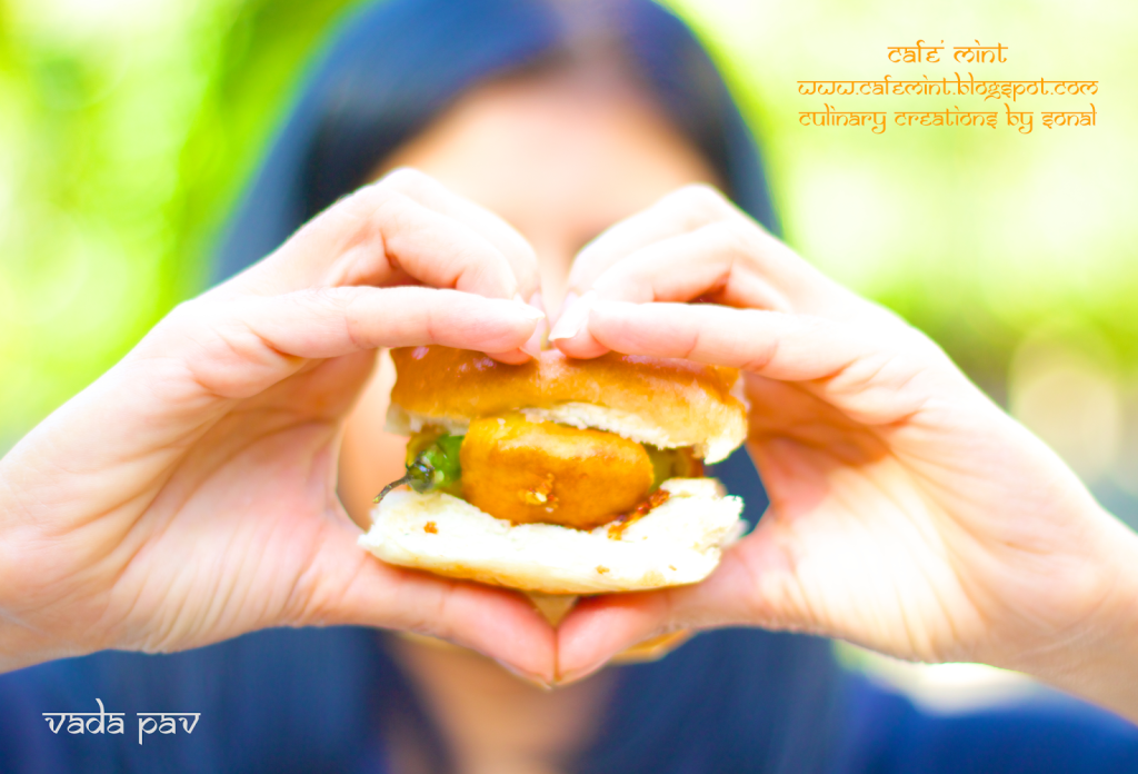 A person forming a heart shape with both hands, holding vada pav in the middle of the heart