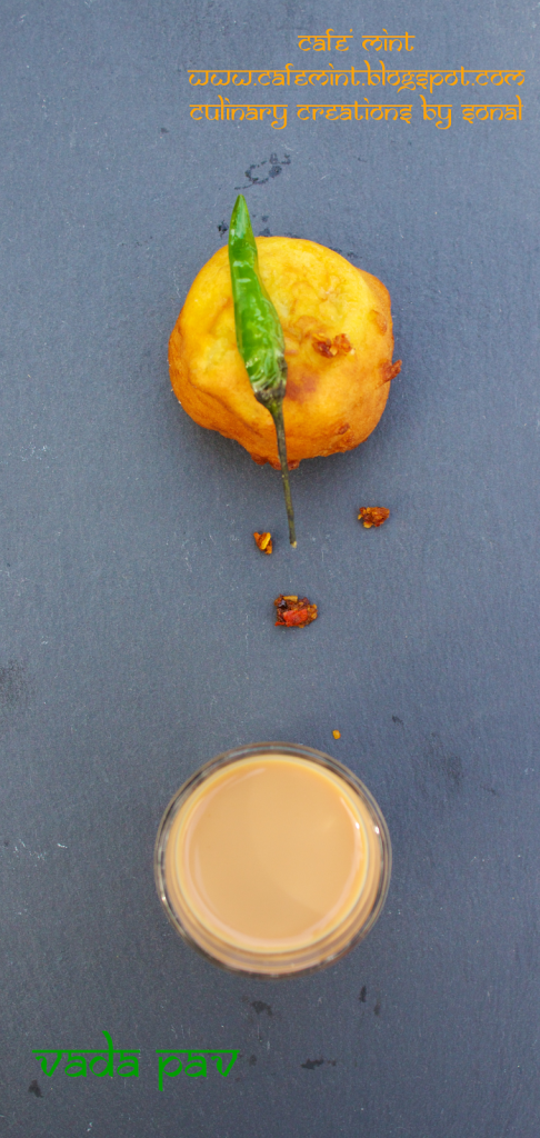 An overhead shot of vada pav with red chutney flakes and green chili on top with a glass of indian masala tea on side, all served on a black chalkboard plate